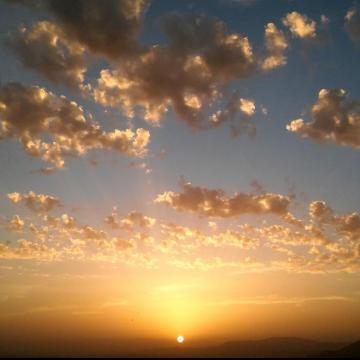 Atardecer en Granada. El sol se pone bajo un cielo moteado de nubes. 15 de Agosto de 2017, Manuel Adán